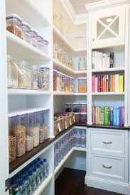 Clear food storage containers, such as glass jars, and cookbooks organized  by color helped make this pantry the most popular photo of