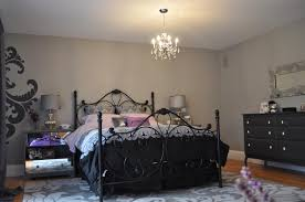 crystal chandeliers over black metal bed added by twin grey table lamps and grey