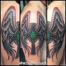 кельтский крест с крыльями и клевером тату на плече у парня