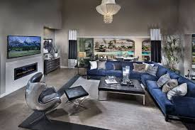 blue sofas living room: expansive open living room on grey tile flooring features lengthy blue fabric sectional sofa and