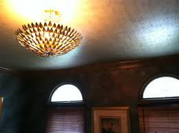 Cool light fixture and gold foil wallpaper on the