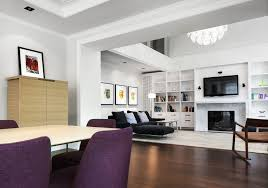 large living room interior having white lacquer tall narrow cabinet shelves flanking modern electric fireplace under