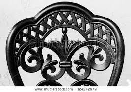 black wrought iron furniture. close up of the back a wrought iron chair in black and white against furniture