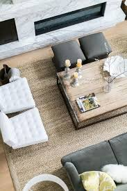 a reclaimed wood box frame coffee table is placed on a seagrass rug and surrounded by a dark gray velvet roll arm sofa two white leather tufted chairs