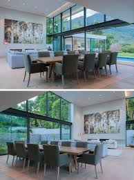 large sliding glass doors can be opened on either side of this modern double height combined living and dining room on one side is the swimming pool and on