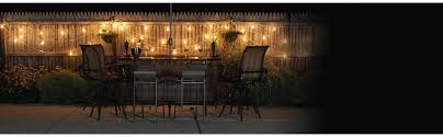 outdoor seating area with string lights on fence