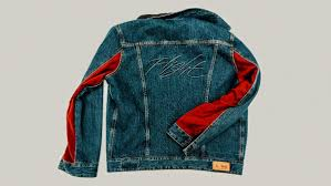 one side of the jacket features levi s classic denim texture with red flight suit accents on the arm and the other boasts the classic nylon look complete