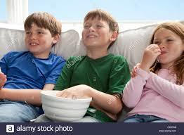 kids watching tv and eating. stock photo - three kids are sitting on the couch watching tv and eating popcorn d