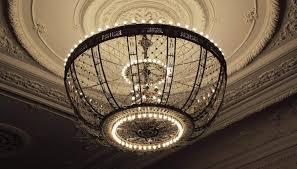 chandelier hanging from large ornamental ceiling medallion