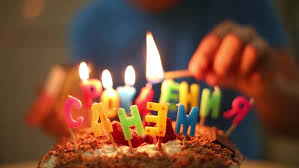 a boy lights a candle in the form of inscriptions happy birthday on the cake
