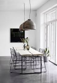 minimalist scandinavian dining room with hanging pendant lights room has white walls and concrete floors wire chairs and a simple wooden table top