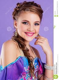 beautiful fashion belly dancer with nice makeup and heardress is wearing a colorful fashion costume isolated on purple