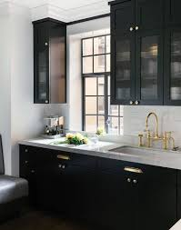 black cup pulls on white cabinets. black kitchen features glass reeded upper cabinets and lower adorned with polished brass hardware paired white marble countertops a cup pulls on ,