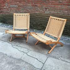 pair of woven rope and wood folding chairs in the manner of hans wegner