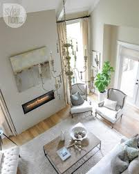 purity designs two story living room features cathedral ceiling accented with candle chandelier over linen bergere chairs flanking fiddle leaf fig plant
