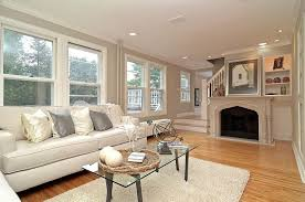 delightful living room design with white fireplace and white leather sofa also laminated wooden floor feat glass coffee table idea