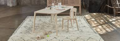 dining tables a light wood table and chair are set atop a white and blue rug with