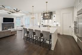 the kitchen features mixed metal accents with yellow gold light fixtures satin nickel cabinet hardware