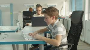 wide angle view busy design office. Young Boy And Girl Sitting For The Desk, Looking In Screen Typing On Wide Angle View Busy Design Office W