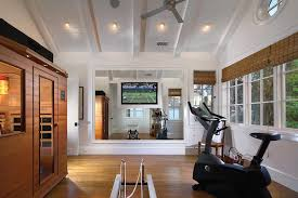 gyms with a sauna with traditional home gym also ceiling fans exposed beams exposed ceiling beams hardwood flooring home gym equipment large wall mounted tv