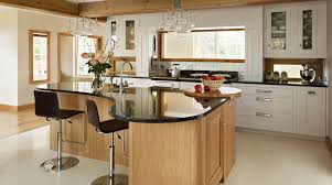 L shaped brown wooden kitchen island with black countertop ...
