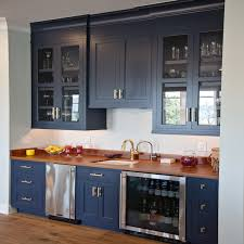 navy wet bar cabinets with wood countertops and stainless steel mini fridge