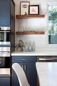 Fantastic kitchen features navy blue shaker cabinets adorned aged brass  pulls paired with white quartz countertops