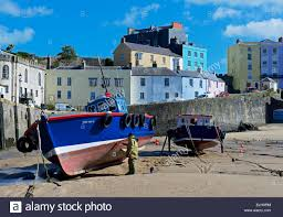 man painting fishing boat on the beach in tenby harbour pembrokeshire wales uk