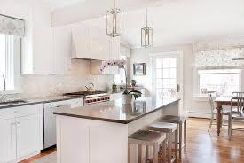 white kitchen with gray quartz countertops and a white glass iridescent tile backsplash