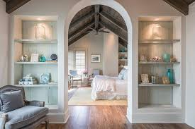 an arched doorway to a bedroom is flanked by built in bookcases lined with distressed plank boards