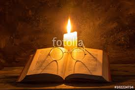 open old book with reading gles and candle