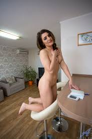 Brunette teaser Tanya S reveals her petite body in a chair before.