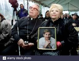 Sophia Lambert (R) of Los Angeles, California, holds a portrait of her late  son Andrew as she sits with her husband, Father Peter Lambert during a  World AIDS Day 2001 observance at