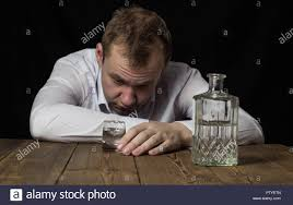 Wooden Table Drunk Is Of In 221880533 Photo A Background Stock Black Shirt - Holding Bottle Alamy Man On Alcohol White Glass