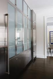 stainless steel kitchen cabinets are located beneath stacked frosted glass cabinets flanked by stainless steel refrigerators placed under stainless steel