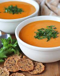 two bowls of ernut squash sweet potato carrot soup sitting on a brown wooden table with