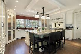 White kitchen with large square white island and dark stools.