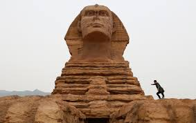 fake wonders of the world in a man poses for photographs on a full scale replica of the sphinx that is part of an unfinished theme park that will also accommodate the production of