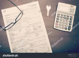 home loan form on desk with gl key and calculator viewed from above