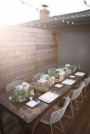 rustic outdoor dining with a long wood table white mesh metal chairs as interior