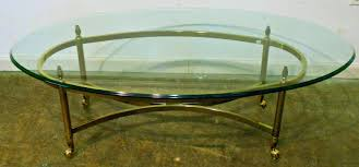 glass topped coffee table oval top with brass frame and wheels for contemporary living room spaces