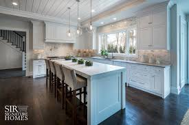 white kitchen island with thick marble countertop and gray velvet counter stools