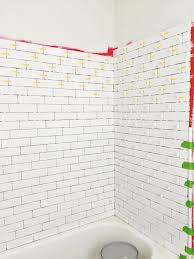 tiling master bathroom tub surround with long white subway tile waterproofing and tiling bathtub shower