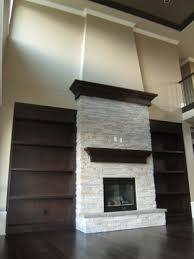 soaring fireplace dark wood bookcases flank white stone fireplace
