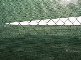 wire fence covering. Torn Green Fabric Covering Chain-link Fence Wire