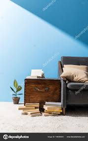 old wooden chest books couch front blue wall stock photo