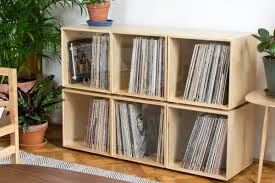 A stackable storage cube contains a collection of vinyl records.