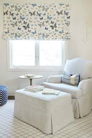 ... nursery features a nursing corner filled with a terry cloth roll arm  glider and ottoman placed in front of windows dressed in a butterflies roman  shade.