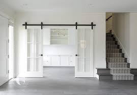 white home office with glass paned sliding doors on rails