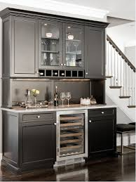 Traditional brown floor home bar idea in Boston with glass-front cabinets,  black cabinets